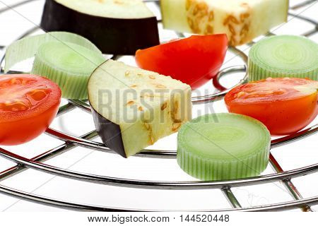 Piece of raw vegetables on grill rack isolated over white background