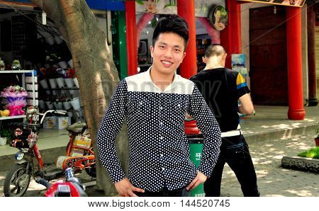 Pixian China - March 27 2013: Chinese youth with a friendly smile standing in front of a shop on the town's main street