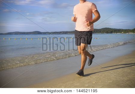 Young man running on the beach at surise