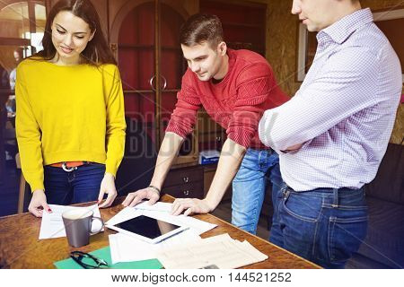 Business team at work with financial reports and a tablet computer