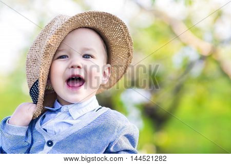 Portrait of a cute happy caucasian baby boy in spring park looks at camera