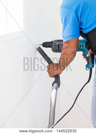 Asian Man Drill On White Wall And Cleaning Dust With Vacuum Together