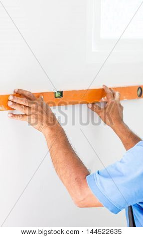Asian Mans Hand Measuring A Wall With Spirit Level