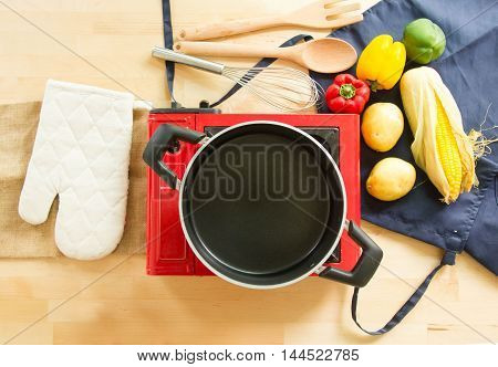 Top View Of Empty Pot And Food Ingredients With Kitchen Utensils For Cooking On Wooden Table