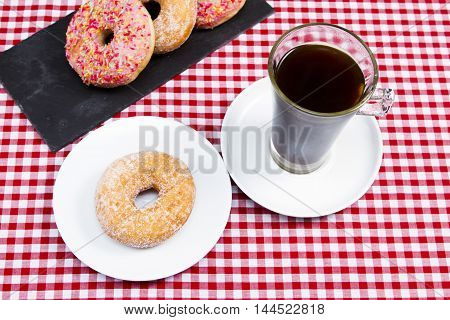 Coffee and Donuts A snack of coffee and donuts on a tablecloth