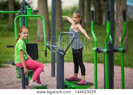 Two funny little girls is engaged in sports equipment outdoor.