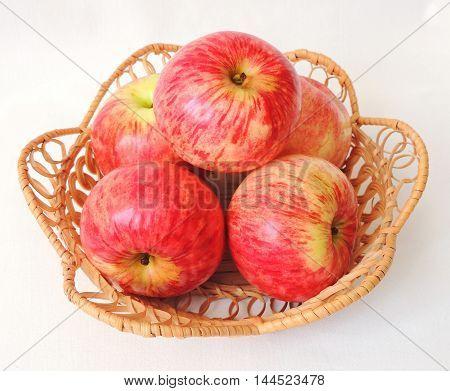 Garden fresh ripe red apples in a wicker basket.
