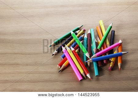 Pile of Color Pencils on Wooden Background