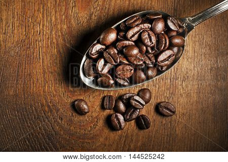 Coffee beans in spoon on wooden background.