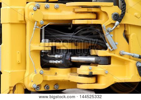 Modern hydraulic mechanism of the yellow tractor.