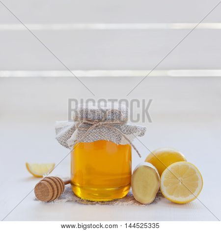 Natural honey in a pot or jar with twine tied in a bow, honey dipper, lemon and ginger on a white wooden background.