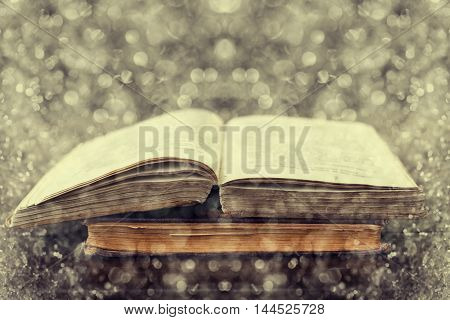 Open old vintage books on wooden background with fantastic double exposure effect using photo of snow bokeh. Reading and education concept.