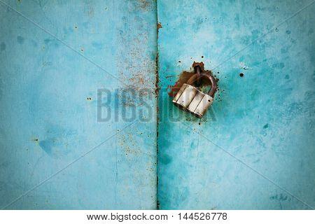 Outboard lock or padlock on vintage metal background.