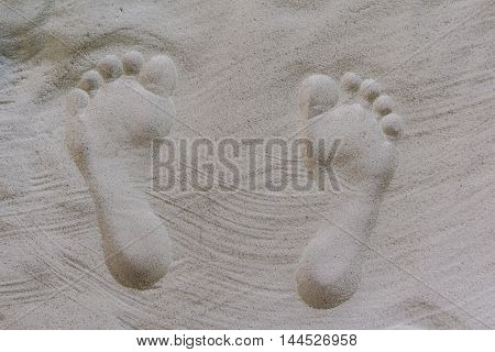 Two well-shaped shaped human footprints in the sand