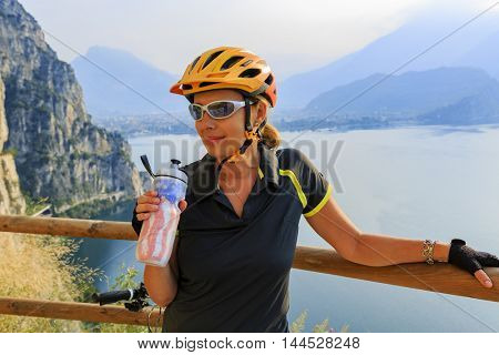 Woman in cyklist helmet on Sentiero della Ponale, Riva del Garda, Italy. Amazing view of Lake Garda in background.
