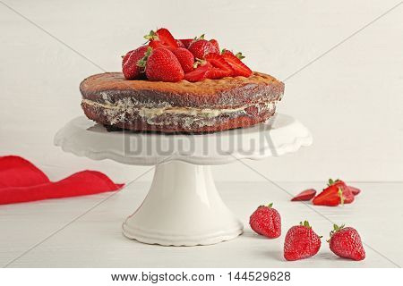 Delicious cake decorated with strawberry on white stand