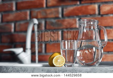 Jar with water and lemon on kitchen table