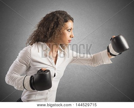 Businesswoman with boxing gloves gives a punch