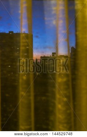 Montevideo cityscape scene at sunset from window curtain view