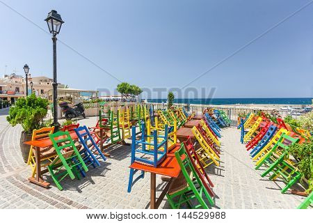 Rethymno, Island Crete, Greece, - July 1, 2016: View of the cafe with color chairs which is located near the embankment of Mediterranean Sea. Rethymno is an old historic town on the northern coast of the island Crete.