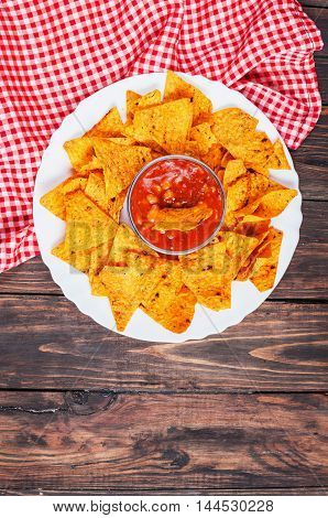 Nachos corn chips with spicy sauce on the table