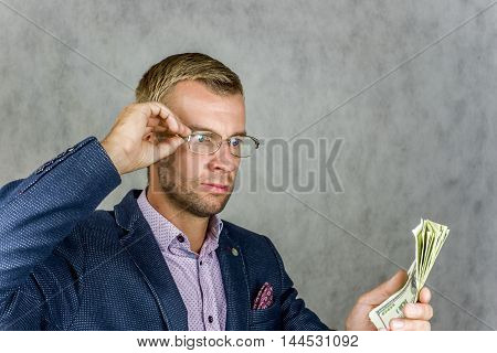 Businessman holding money and looking carefully at them, on a gray background