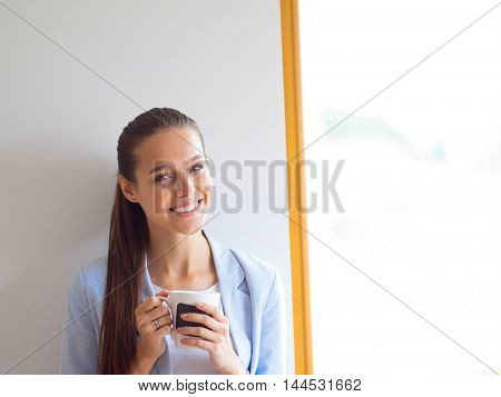 Attractive woman sitting at desk in office having takeaway coffee.