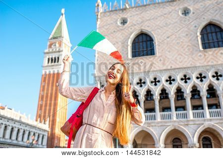 Young female traveler waving italian flag on San Marco square in Venice. Happy vacations in Venice