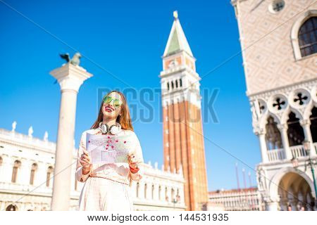 Young female traveler standing with paper map on San Marco square in Venice. Happy vacations in Venice