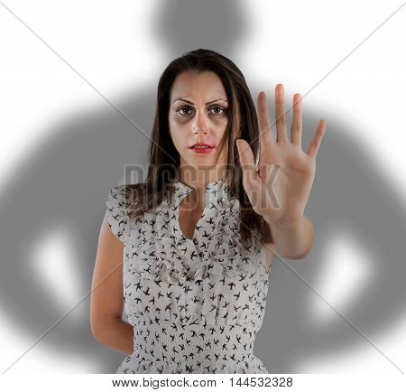 Scared woman with bruises and scratches with shadow of a man behind her