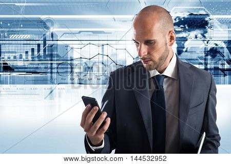 Businessman looks at the screen of his cellphone