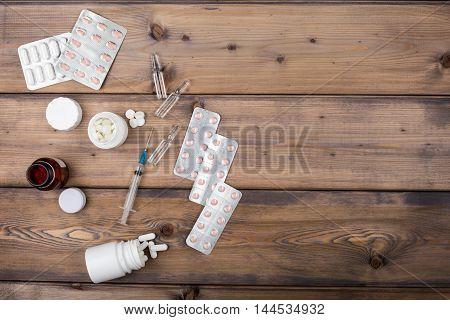Medicine setup. Syringe and ampule on wooden background