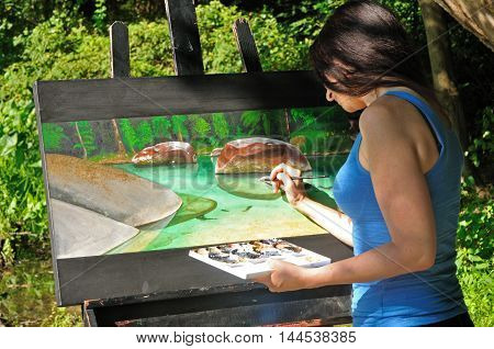young female artist working on acrylic painting of nature scene outside