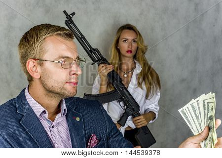 Businessman holding money and looking at them in the background girl with a machine gun on a gray background