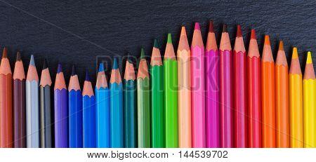 Back to school pencils rainbow border on black board background