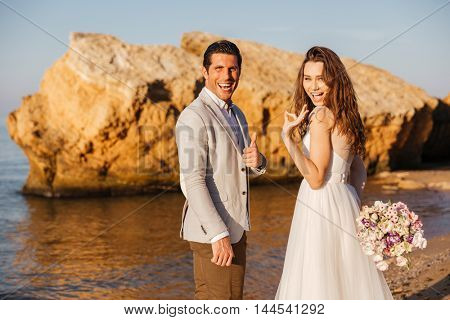 Just-married couple walking at the beach and showing ok sign holding bouquet