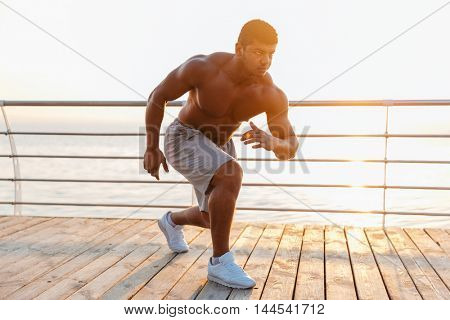 Attractive shirtless african american young man athlete warming up and training on pier