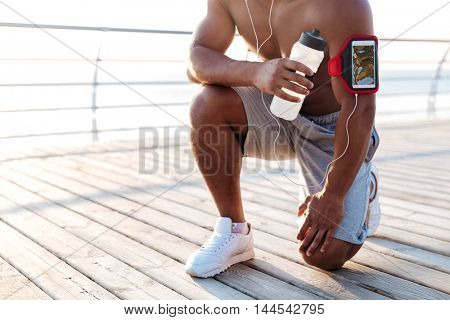 Closeup of shirtless african american young sportsman training and drinking water on pier