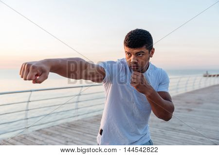 Focused african american young man athlete working out on pier in the morning