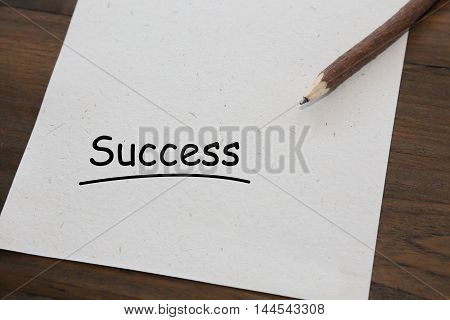 background of pencil with word success on old wood table