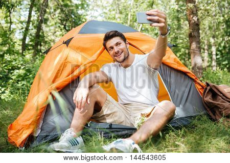 Happy young man tourist sitting and taking selfie with cell phone in forest