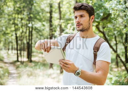 Serious young man with backpack using tablet outdors