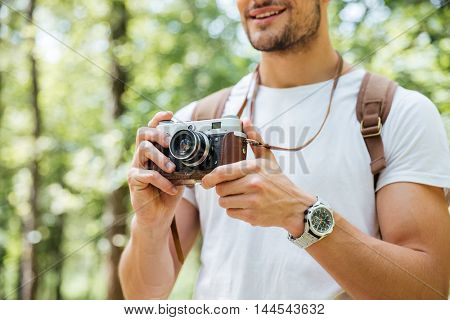 Closeup of smiling young man with backpack standing and taking photos with vintage camera outdoors