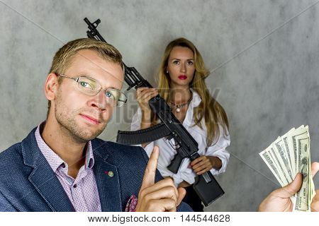 Businessman holding money and looking at their finger up in the background beautiful girl with a gun on a gray background