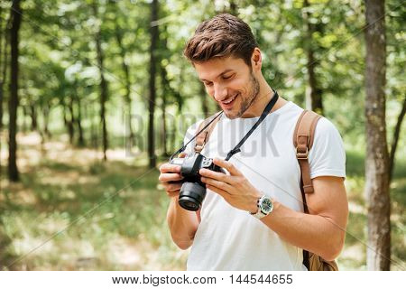 Smiling young man photographer standing and using modern photo camera in forest