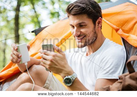 Happy young man tourist charging battery of mobile phone in touristic tent in forest