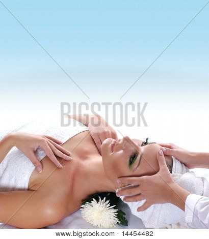 Young attractive sexy blond getting spa treatment over blue background