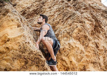 Young brunette man climbing natural rocky wall