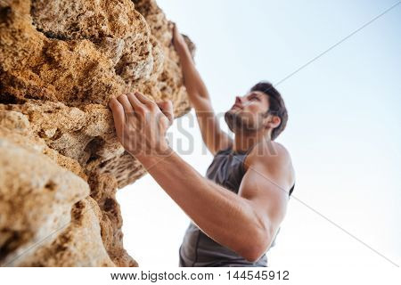 Young brunette man climbing natural rocky wall