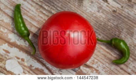 One large organic ripe tomato and two sharp green chili pepper on a rustic wooden kitchen table, top view